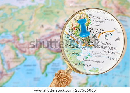 Blue tack on map of the world with magnifying glass looking in on Singapore - stock photo