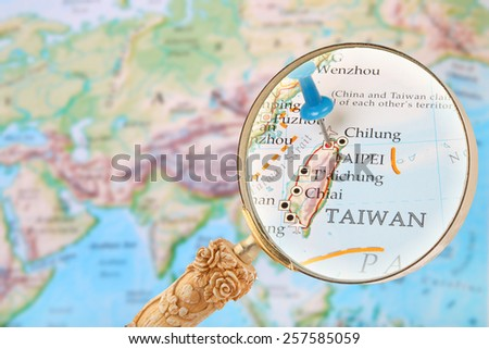 Blue tack on map of the world with magnifying glass looking in on Taipei, Taiwan - stock photo