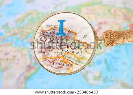 Blue tack on map of the world with magnifying glass looking in on Tbilisi, Georgia - stock photo