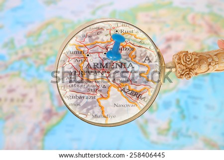 Blue tack on map of the world with magnifying glass looking in on Yerevan, Armenia - stock photo