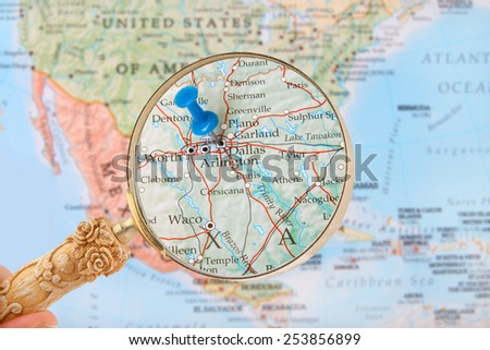 Blue tack on map of United States of America with magnifying glass looking in on Dallas, Texas - stock photo