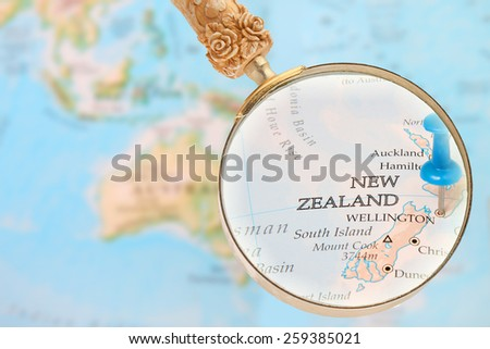 Blue tack on map  with magnifying glass looking in on Wellington, New Zealand - stock photo