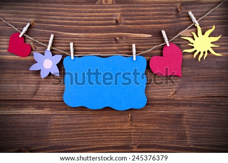 Blue Tag Or Label With Hearts And Flower And Sun On A Line With Copy Space For Your Free Text Here On Wooden Background, Four Symbols, Vintage, Retro And Old Fashion Style With Frame - stock photo