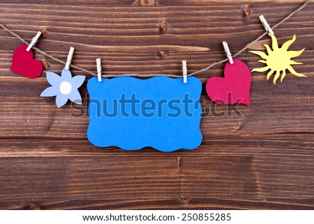 Blue Tag Or Label With Hearts And Flower And Sun On A Line With Copy Space For Your Free Text Here On Wooden Background, Four Symbols, Vintage, Retro And Old Fashion Style - stock photo
