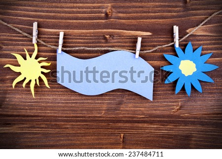 Blue Tag Or Label With Sun And Flower On A Line With Copy Space Or Your Free Text Here On Wooden Background, Two Symbols, Vintage, Retro And Old Fashion Style With Frame - stock photo