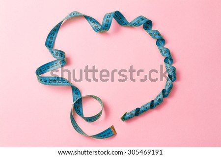 Blue tailor measuring tape on pink background  - stock photo