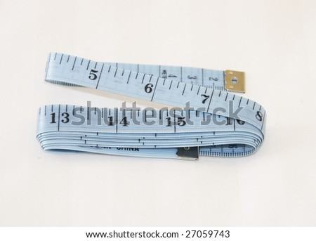 blue tape-measure showing inches and centimetres over a light background