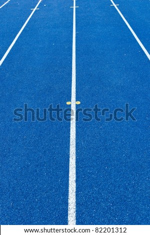 Blue tartan athletic running track texture on the stadium. Tartan track material is the trademarked all-weather synthetic track surfacing for athletics made of polyurethane - stock photo