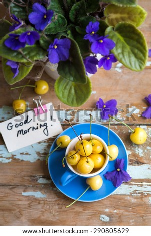 Blue tea cup full with yellow juicy cherries with a good morning note card on a wooden table with violets - stock photo