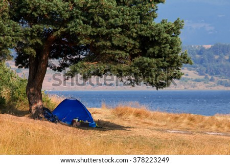 Blue tent near mountain lake, summer time