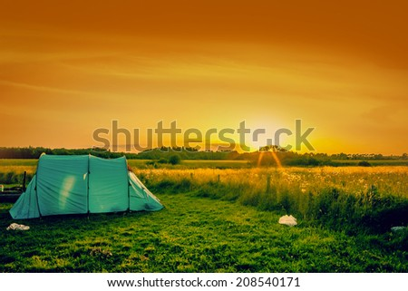 Blue tent on a field at sunrise - stock photo