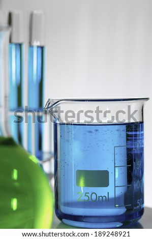 blue test tubes and bottles with white background - stock photo