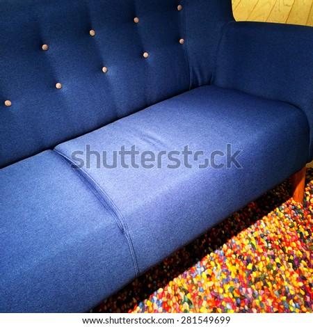 Blue textile sofa on a colorful carpet. Modern furniture. - stock photo
