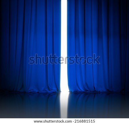 blue theater or cinema curtains slightly open and white light behind - stock photo