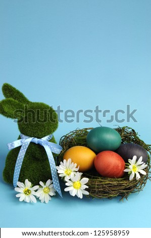 Blue theme Happy Easter scene still life with grass bunny rabbit with rainbow color eggs in a nest with white daisies. vertical with copy space, your text here. - stock photo