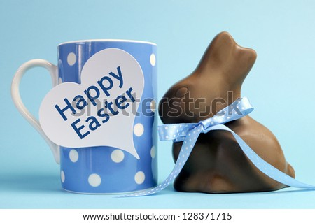 Blue theme polka dot breakfast coffee mug with chocolate bunny rabbit and heart shape message saying Happy Easter. - stock photo