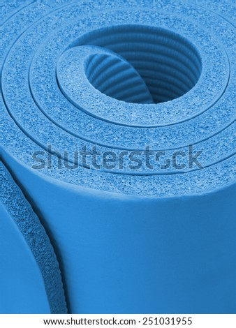 Blue thick exercise or fitness mat rolled up, closeup - stock photo