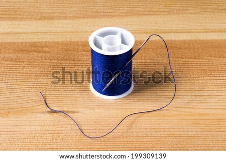 blue thread with a needle - stock photo