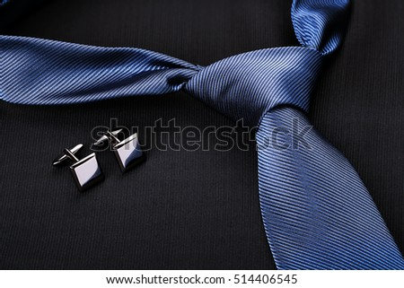 blue tie and cuff links on dark suit