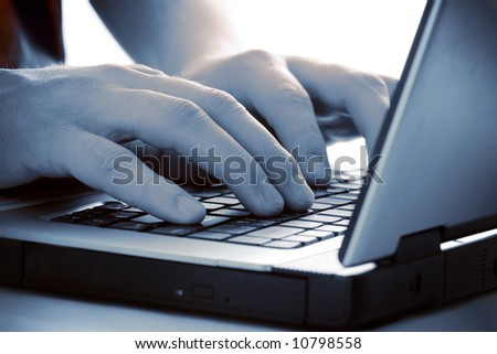 blue tint fingers on keyboard of the laptop