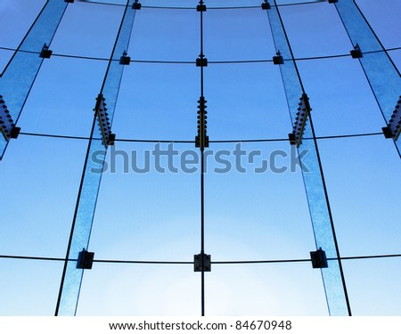 Blue tinted glass wall structure with setting sun causing a glow at the bottom of the image - stock photo