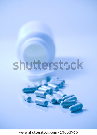 Blue tinted picture of  pills with bottle on reflective surface and with selective focus