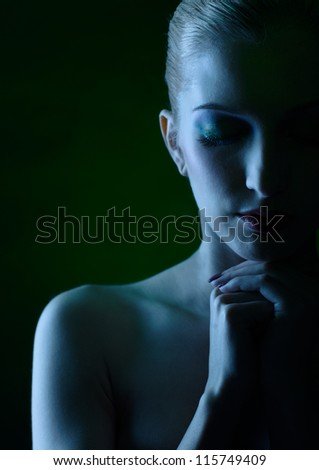 Blue tinted portrait of beautiful young blonde woman in jewelry with hands below her chin