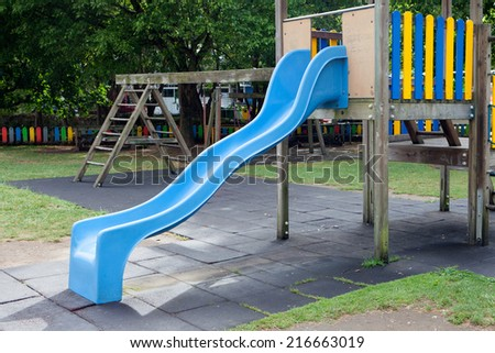 Blue toboggan in the middle of a playground without children - stock photo