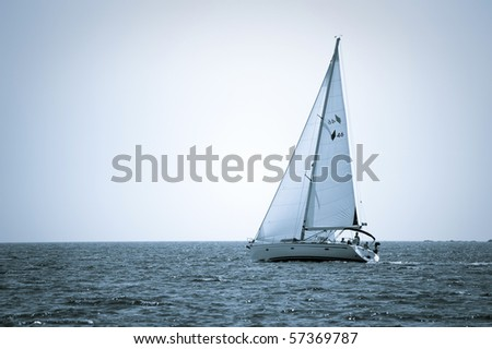 blue tone picture of yacht sailing on the sea - stock photo