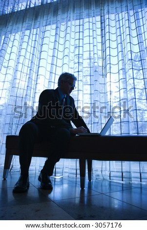 Blue tone silhouetted image of prime adult Caucasian man in suit sitting on bench typing on laptop. - stock photo