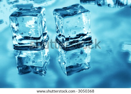 Blue toned ice cubes on reflective surface
