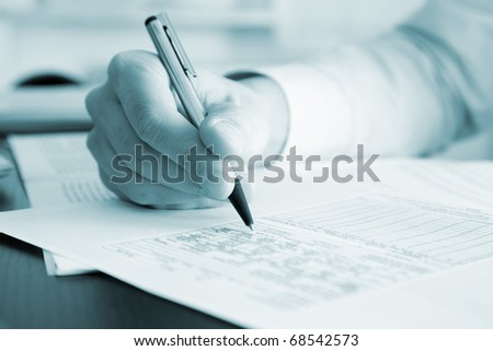 Blue toned image of a businessman writing a document in his office, useful for brochures - stock photo