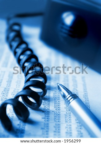 Blue toned image of a financial report and a phone - stock photo