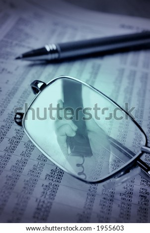Blue toned image of a financial report, phone in a hand reflects in the glasses - stock photo