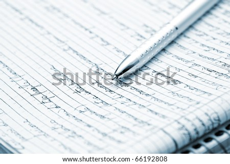 Blue toned image of a silver pen lying on a notebook - stock photo