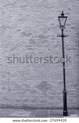 Blue toned image of brick wall and lamp post - stock photo