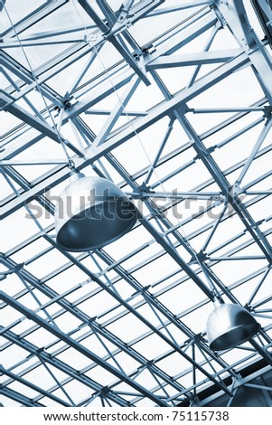 blue toned lamps and metallic girders under glass ceiling of industrial building - stock photo
