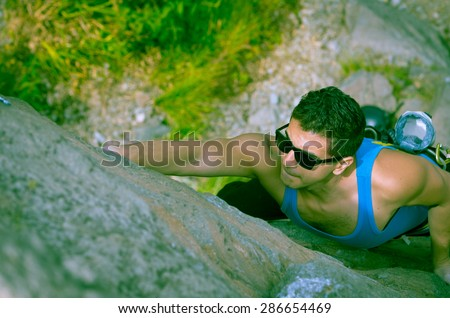 blue toned shot from above angle of man climbing mountain with sunglasses - stock photo