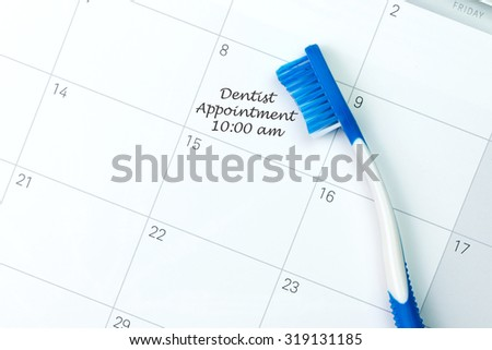 Blue toothbrush on dentist appointment reminder on a calendar - stock photo