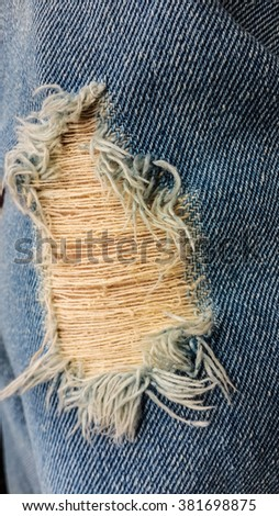 Blue torn denim jeans texture. Outdoors closeup. - stock photo