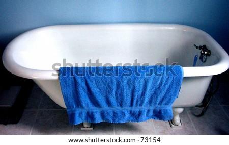 Blue Towel on White Tub - stock photo