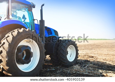 Blue tractor in a field on a bright sunny day - stock photo