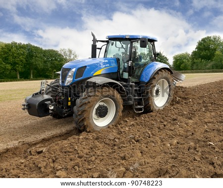 Blue tractor plows field at high speed, readying for harrowing. - stock photo