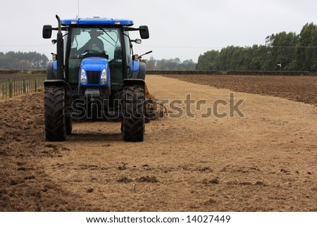 Blue tractor using shallow cultivation tillage on a paddock in Canterbury, New Zealand - stock photo