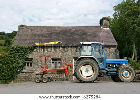 Blue tractor with a red swather (picks up, aerates, and spreads out cut hay). To the rear is a derelict small stone barn