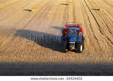 Blue Tractor with red car - stock photo