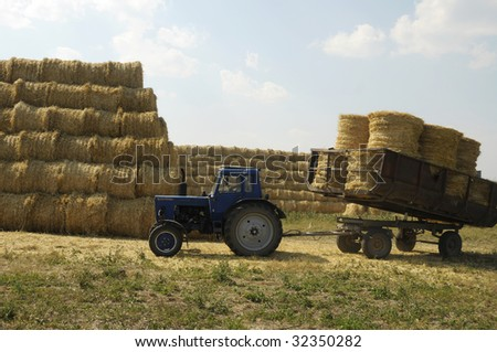 blue tractor with the trailer, loaded with straw sheaves at big stack of straw in background - stock photo