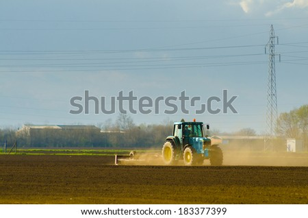 Blue tractor working on the agricultural field on sunny spring day.