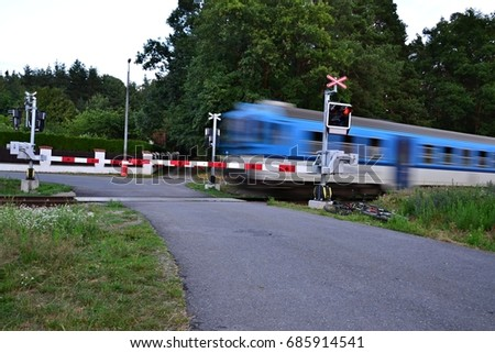 Blue train crossing the road