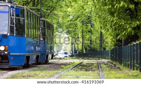 Blue tram driving through green alley in European city of Krakow, Poland - stock photo